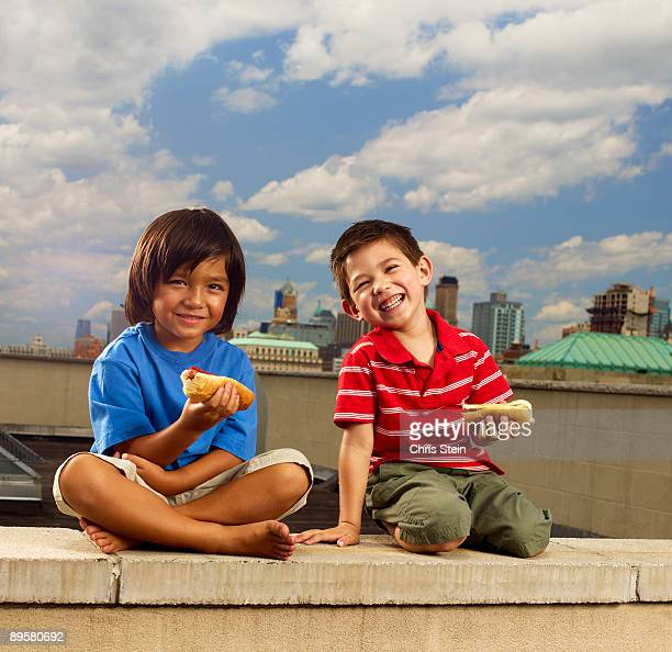 Two Young Boys Eating Hot Dogs