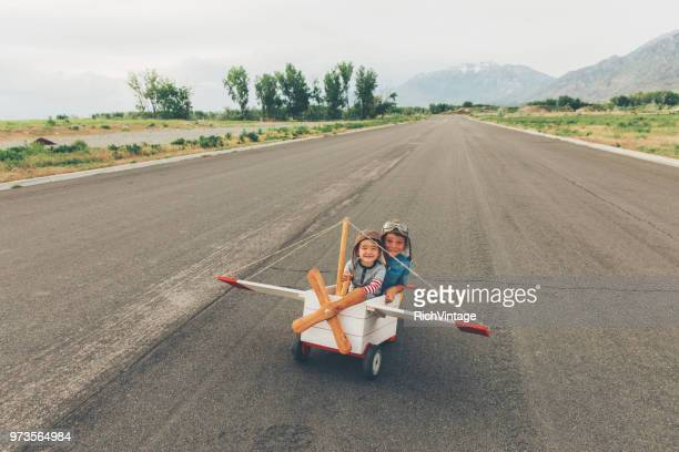 two young boys fly toy airplane - co pilot stock photos and pictures