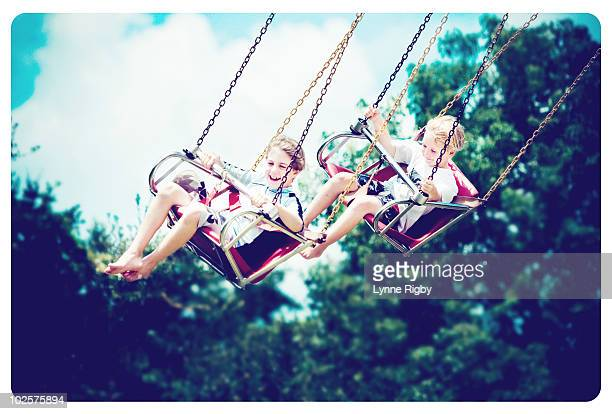 Two young boys flying on the giant swings