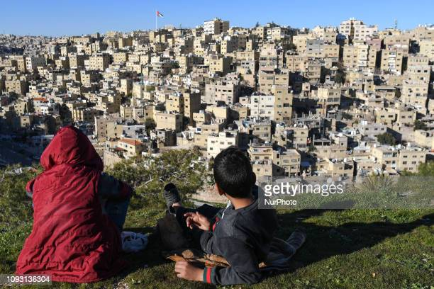 Two young boys having a snack in the Old Town of Amman, near the Citadel historical site. On Saturday, February 2 in Amman, Jordan.