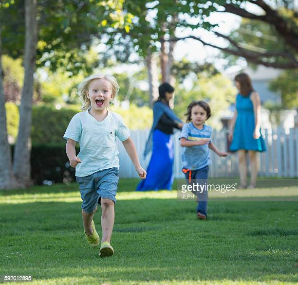Two young boys having race in garden