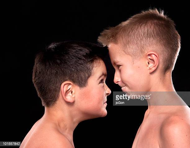 Two young boys head to head, angry