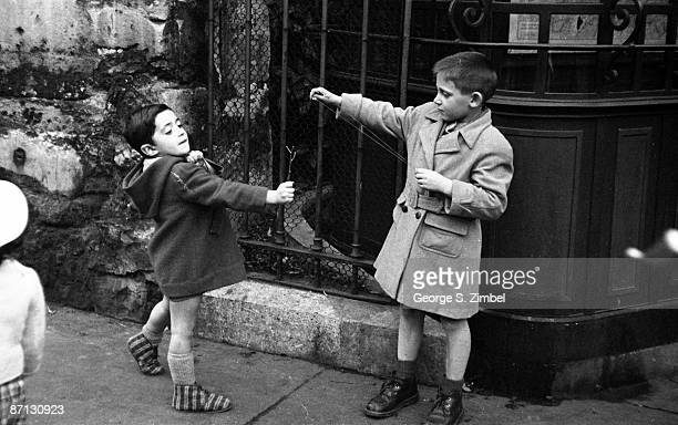 Two young boys horse around and play with slingshots on the sidewalk in postwar Paris 1952