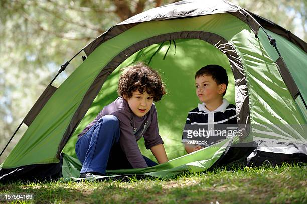 Two young boys in a green tent while camping