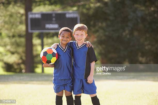 two young boys in soccer gear with ball - soccer scoreboard stock photos and pictures