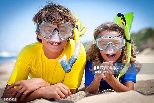 Two young boys in the sand with snorkling masks