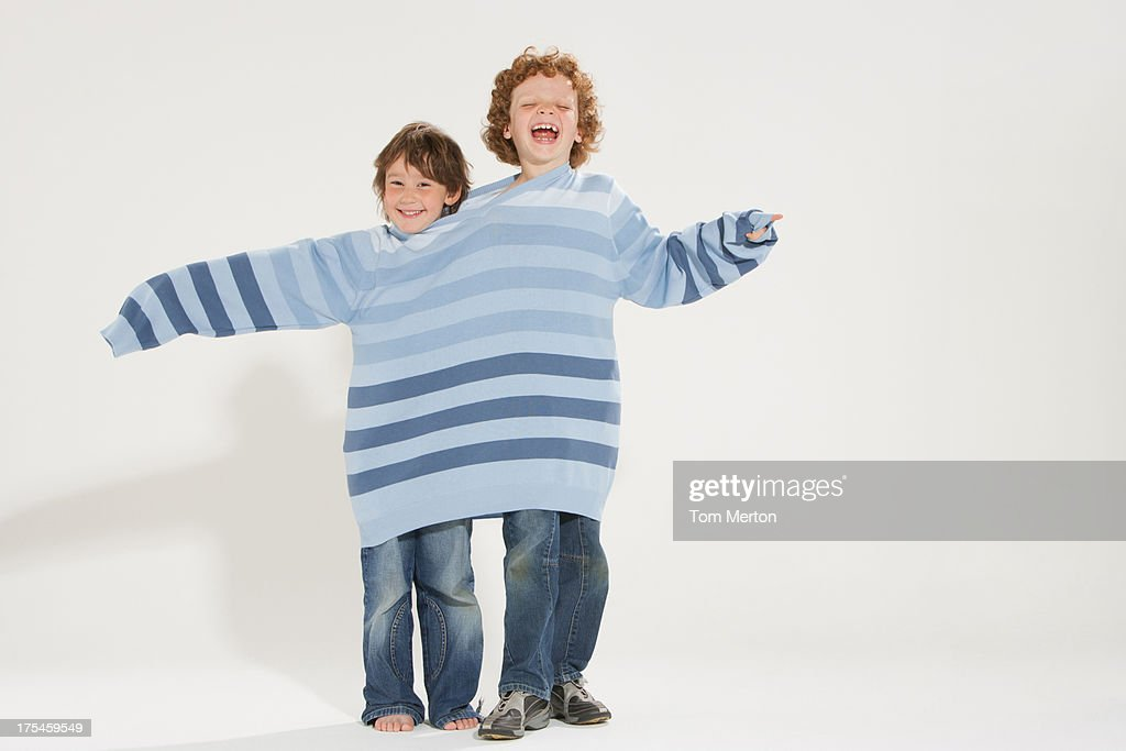 Two young boys indoors wearing the same sweater : Stock Photo