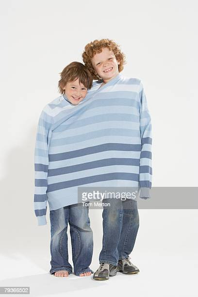 Two young boys indoors wearing the same sweater