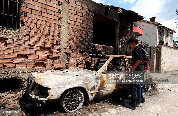 Two young boys look at a burned car in Kumanovo on May 12 2015 Special police units pulled out of the northern Macedonian town early on May 11 where...