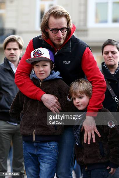 Two young boys look on as people gather to leave tributes at the Place de la Bourse following today's attacks on March 22 2016 in Brussels Belgium At...