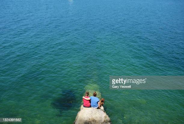 two young boys looking out to sea - white caucasian stock pictures, royalty-free photos & images