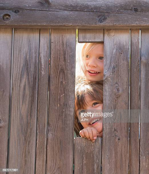 Two young boys looking through hole in fence