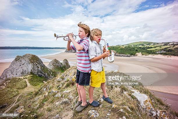 Two young boys making music on a beach holiday