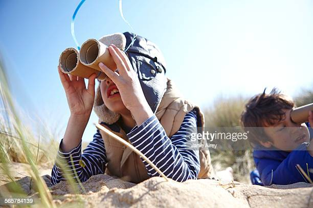 Two young boys on beach, looking through pretend binoculars