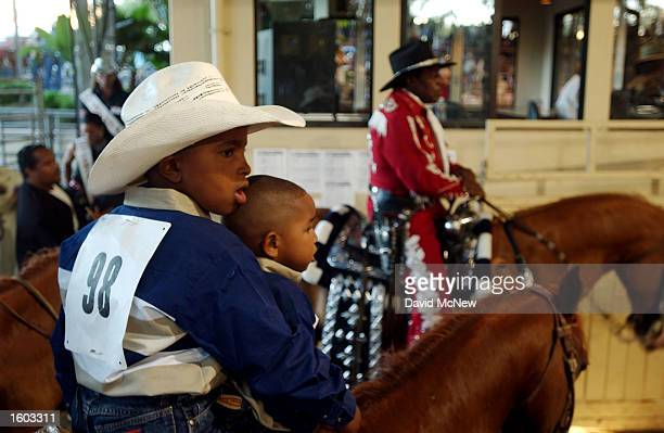 Two young boys participants of the 18th annual Bill Pickett Invitational Rodeo enter the arena July 21 2001 in Los Angeles CA The rodeo is named for...