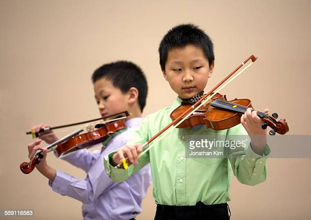 Two young boys play violin