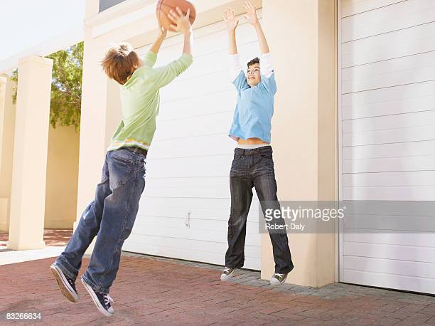 Two young boys playing basketball