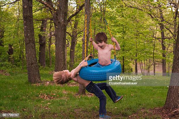 Two young boys playing on tyre swing in forest