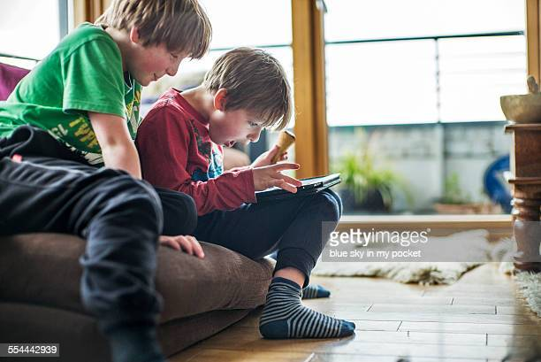 Two young boys playing with a tablet computer.