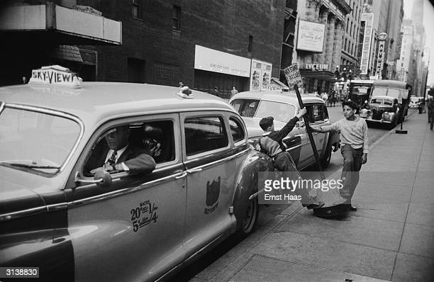 Two young boys playing with a taxi rank sign on West 45th Street Manhattan New York June 1951 In the background is the Lyceum Theatre with a poster...