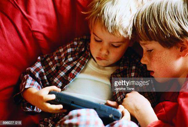 Two young boys (4-9) playing with electronic game