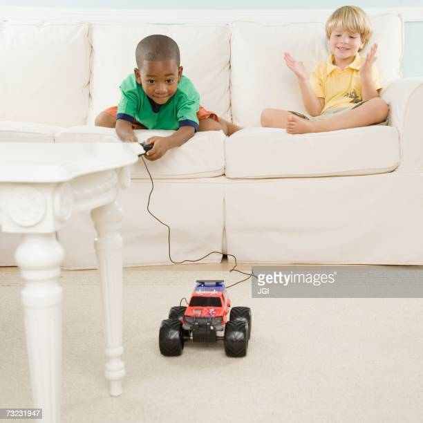 Two young boys playing with remote control car in living room