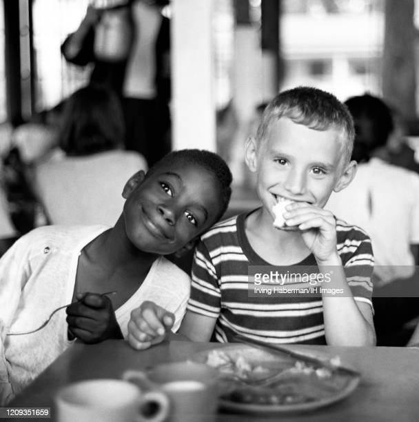 Two young boys pose as they have lunch together at an Inter-Racial Camp run by Christian Herald circa 1948 in New York, New York.