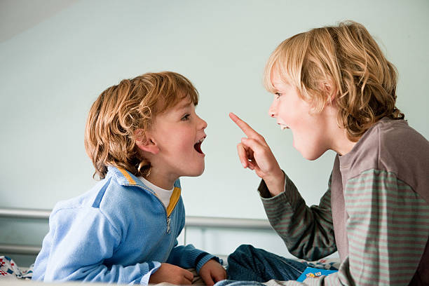 two young boys quarrelling - siblings fighting stock pictures, royalty-free photos & images