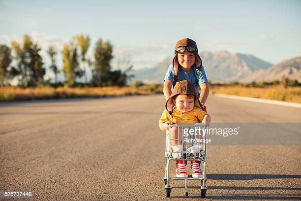 Two Young Boys Racing Shopping Cart