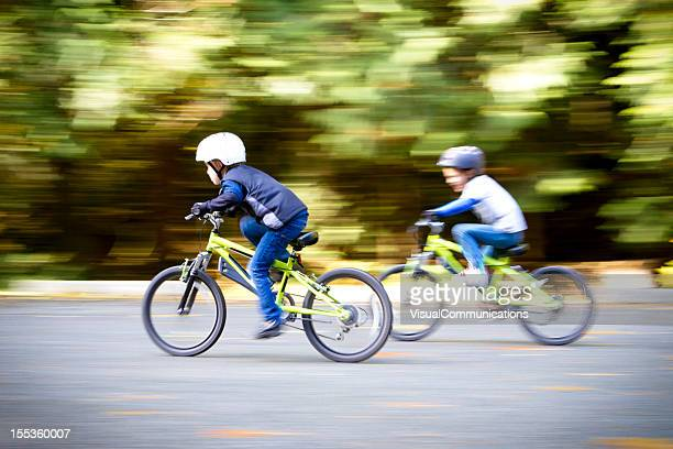 Two young boys racing their bikes.
