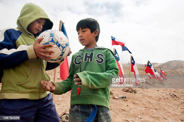 Two young boys relatives of one of the trapped miners play with a football at the top of the hill above Campanento Esperanza at the San Jose Mine in...