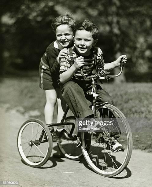 Zwei Jungen (6 – 7) riding Dreirad im park (B & W), Porträt