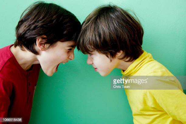 two young boys screaming and fighting and clashing violently - menselijk lichaamsdeel stockfoto's en -beelden