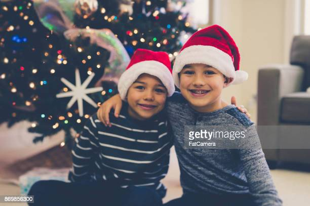 Two young boys sit in front of Christmas tree wearing elf hats