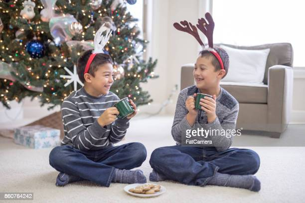 Two young boys sit in front of Christmas tree wearing reindeer antlers and holding hot chocolate mugs.