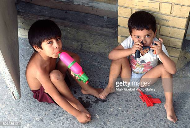 Two young boys sit on the ground and play, Juarez, Mexico, late 1980s.