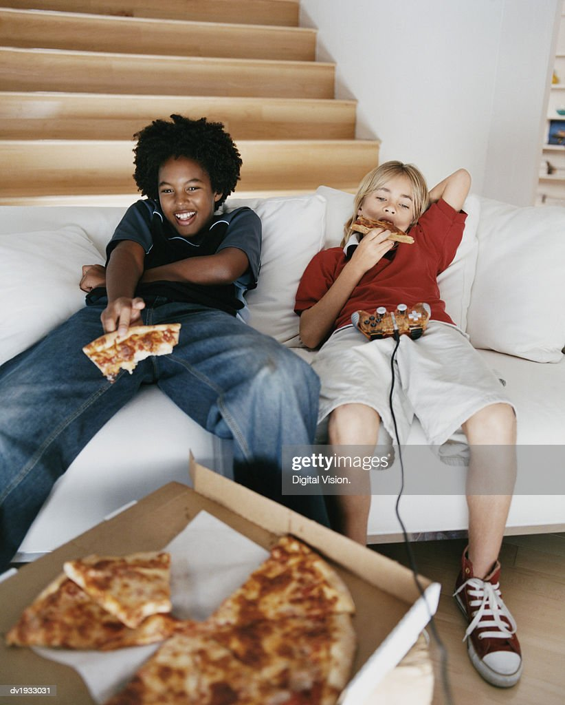 Two Young Boys Sitting on a Sofa and Eating Slices of Pizza : Stock Photo