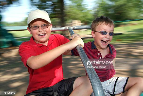 Two Young Boys Spinning Fast on a Merry Go Round