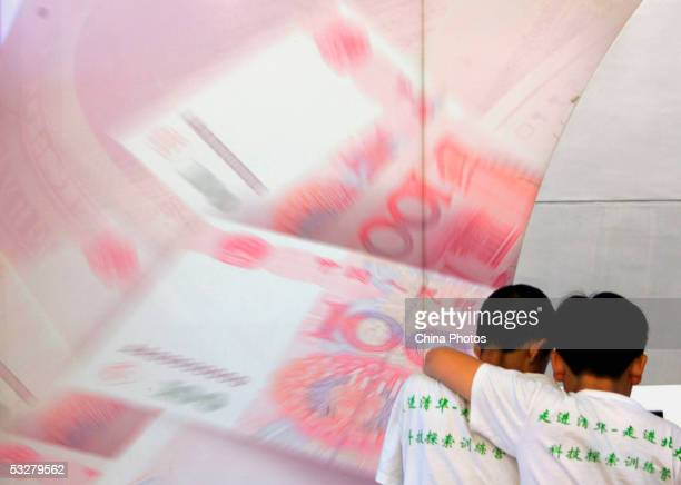 Two young boys stand in front of a billboard featuring 100 yuan notes at an exhibition of the Chinese currency Yuan at the Beijing Science Museum on...