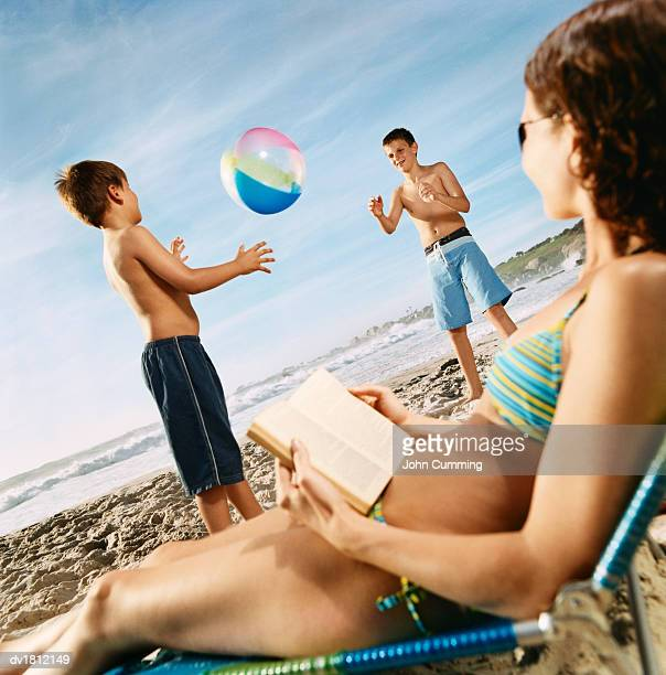 Two Young Boys Stand on the Beach Throwing a Beach Ball to Each Other, Their Mother Watching Them From Her Sun Lounger