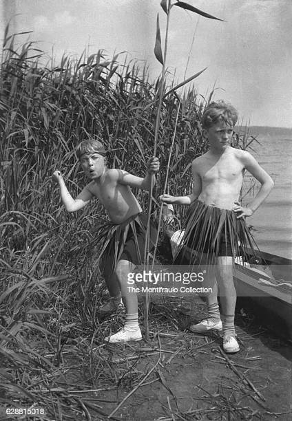 Two young boys standing among rushes by a lake stripped down to shorts wearing hula type skirts giving the appearance of tribal natives one boy...