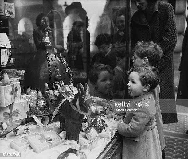 Two young boys stare longingly at Easter confectionary on display in a shop window 22nd March 1952