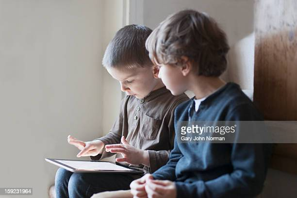 two young boys using digital tablet