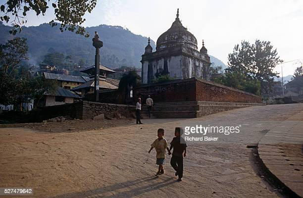 Two young boys walk downhill passing the Rameshwar Mahdev temple in Kathmandu Nepal Holding hands the friends make their way back towards the city...