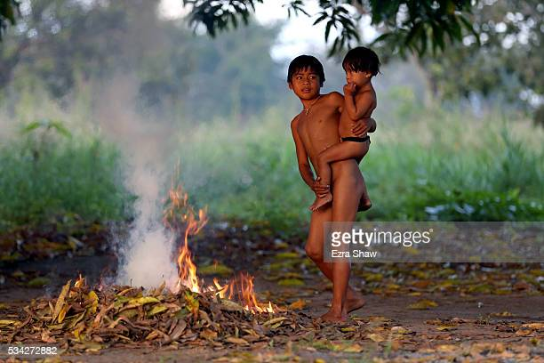 Two young boys warm up by a fire behind their home after a swim in the lake on May 7 in Kamayura Brazil