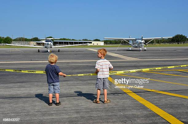 two young boys watching small aircraft - lynn pleasant stock pictures, royalty-free photos & images