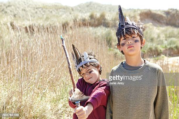 Two young boys wearing fancy dress, holding home-made bow and arrow