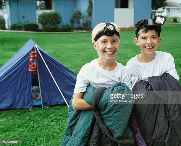 Two Young Boys Wearing Head Torches Stand Side by Side in Sleeping Bags, in Front of a Tent in Their Garden