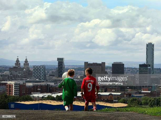 Two young boys wearing the football strip of Liverpool FC walk through Everton Park with the city of Liverpool ahead of them on August 13 2008 in...