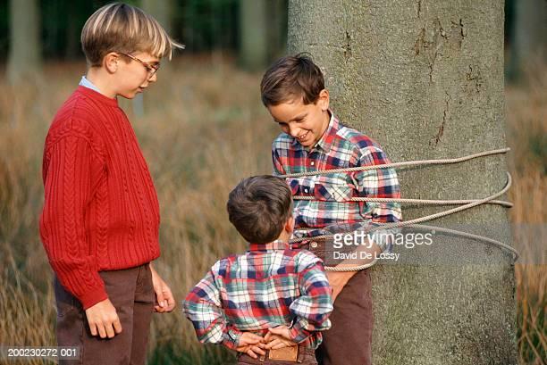 two young boys (6-7) (12-13) with friend (10-11)  tied to tree - junge gefesselt stock-fotos und bilder